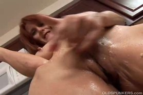 Mature redhead plays with food