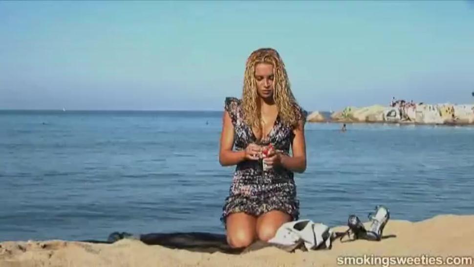 The beautiful blonde girl Vanessa smoking on the beach