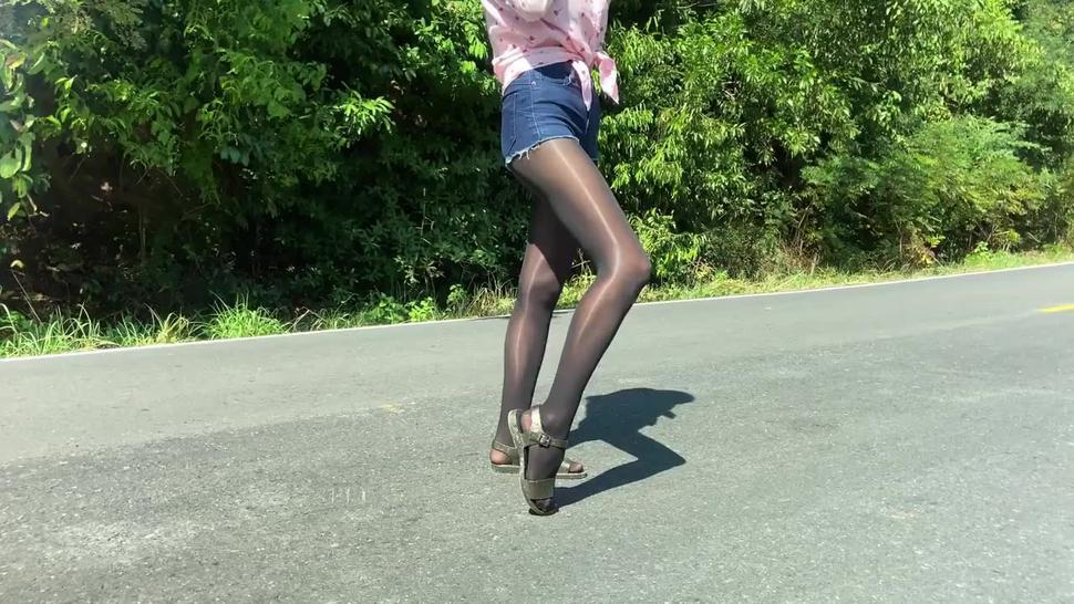 Anna walks on the mountain road in shiny pantyhose