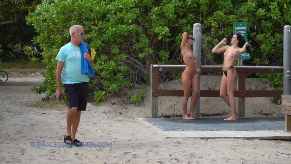 two naked girls showering at the beach