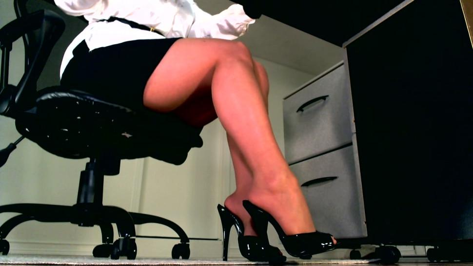 Femdom goddess in shiny pantyhose prefers to keep her slaves under her desk for daily domination