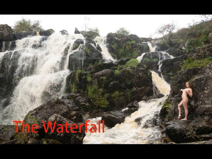 Nude woman bathing with water from a waterfall