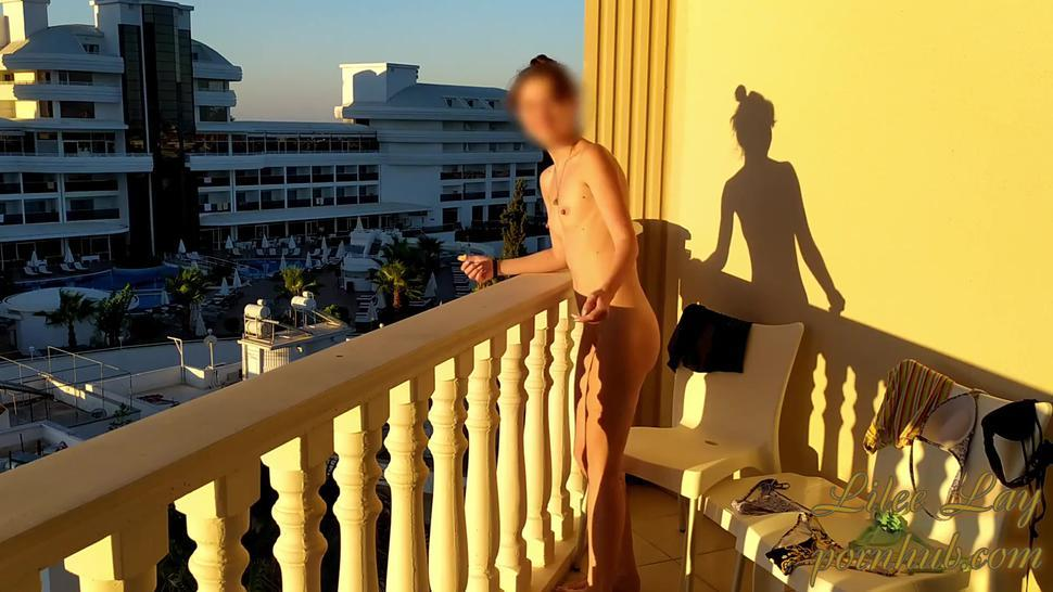 Naked girl on the balcony greets the morning
