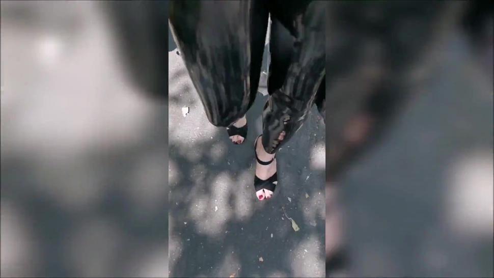 Girl wearing latex leggings and high heels in public
