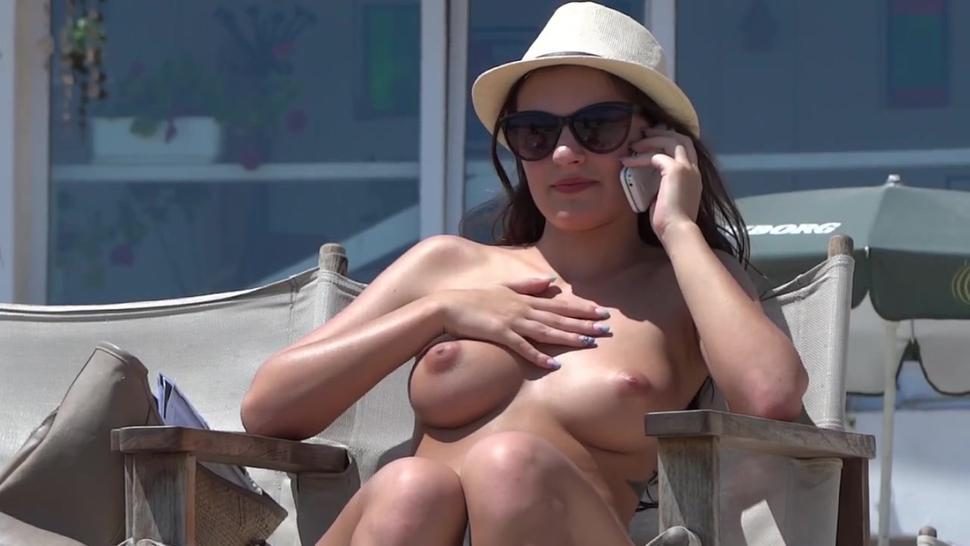 Topless beauty on the Ibiza beach has magnificent breasts... and doesn't she know it!