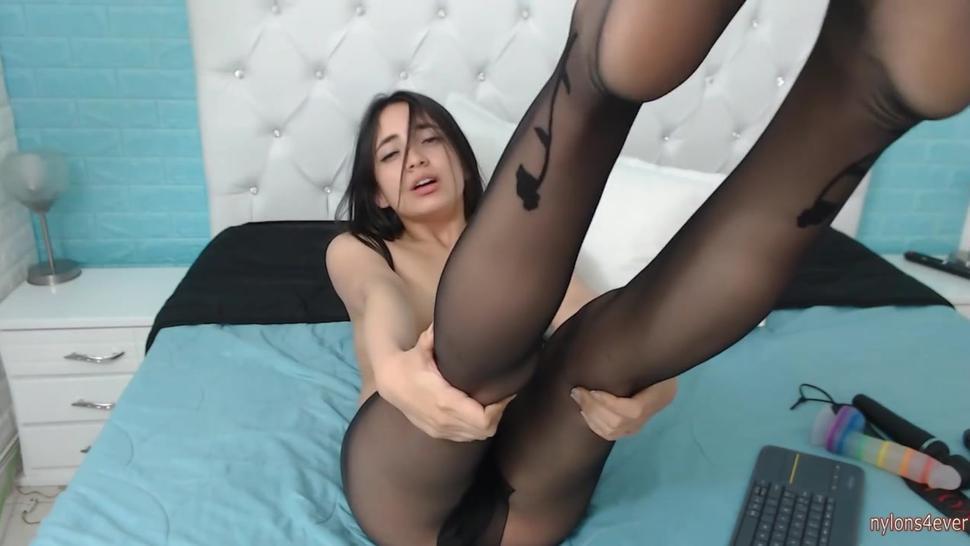 Cute brunette in pantyhose spreads her legs