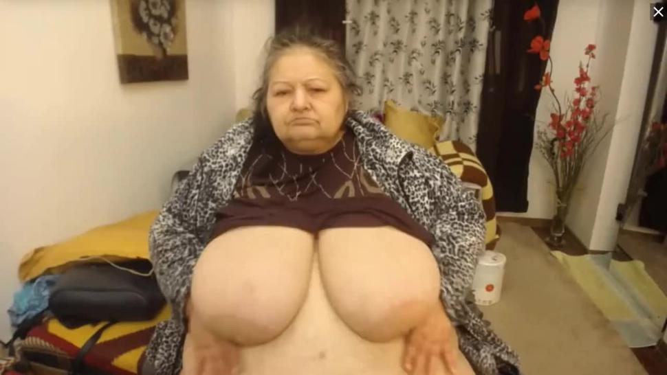 granny holds saggy white boobs up