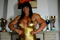 Massive big tittied muscle queen Jana flexes in tight gold dress