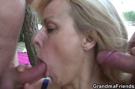 Granny rides and sucks at same time outdoors