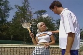 Tennis pro teaches blonde how to volley at the net